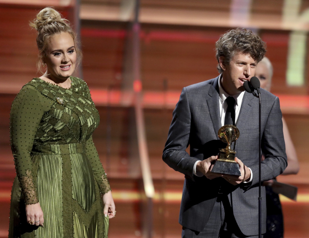 "Greg Kurstin, right, and Adele accept the award for song of the year for ""Hello"" at the 59th annual Grammy Awards on Sunday in Los Angeles. Matt Sayles/Invision/AP"
