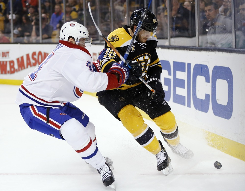 Montreal Canadiens' Paul Byron and Bruins' Kevan Miller battle for the puck during the first period in Boston on Sunday.