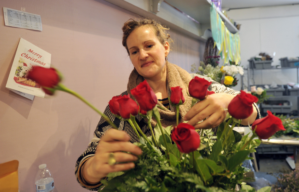 Designer Anne Heelan puts together a floral arrangement Monday at Harmon's & Barton's in preparation for Valentine's Day. Below, designer Jennifer Miller, right, and Heelan work on floral arrangements at Harmon's & Barton's ahead of Valentine's Day on Tuesday.