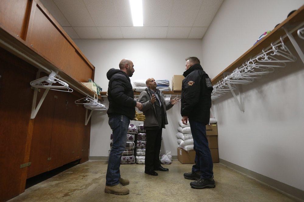 From left, Fadel Alshawwa, Jean Pierre Venegas, manager of the Manitoba Interfaith Immigration Council, and Bill Spanjer, municipal emergency coordinator for Emerson-Franklin, talk as they bring blankets and pillows into a community hall for refugees that may walk across the border in Emerson, Manitoba.