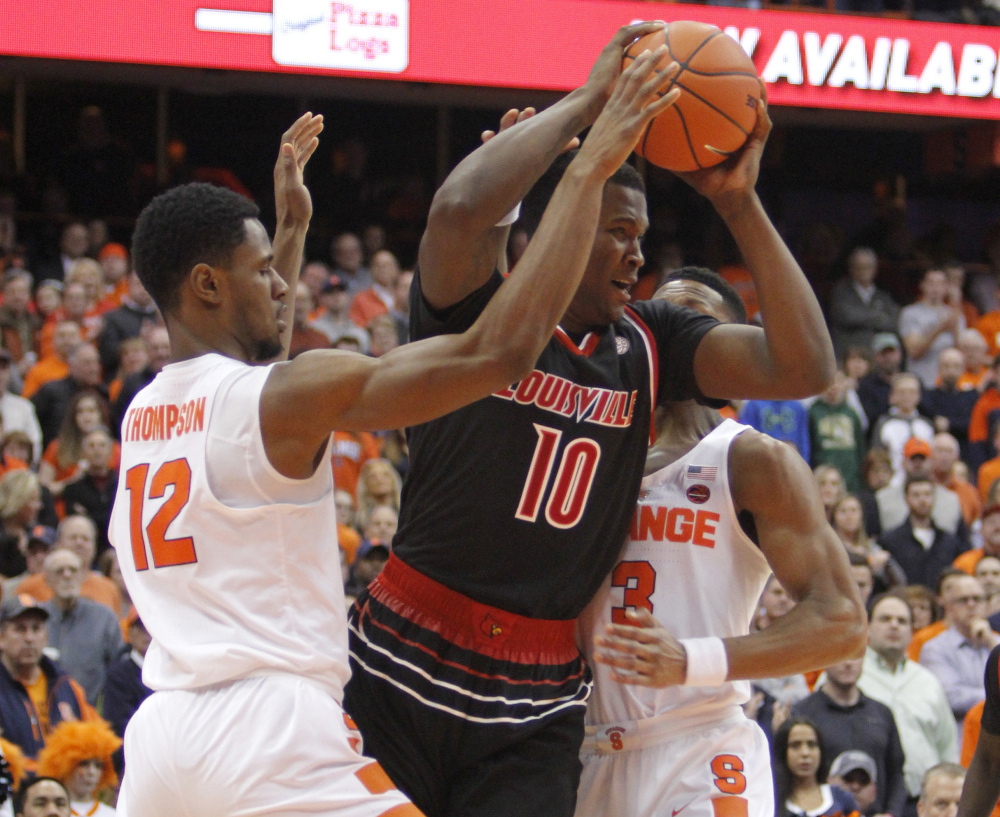 Louisville's Jaylen Johnson, center, is surrounded by Syracuse's Taurean Thompson, left, and Andrew White III, during a 76-72 Cardinals' win at Syracuse, N.Y., on Monday.