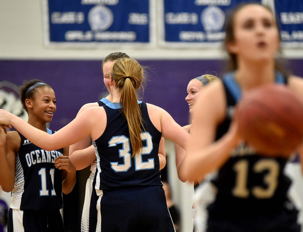 Oceanside players celebrate their impending victory over Waterville as Gabby Simmons sinks both free throws in the final seconds of Tuesday night's Class A North girls' basketball prelim at Waterville.
