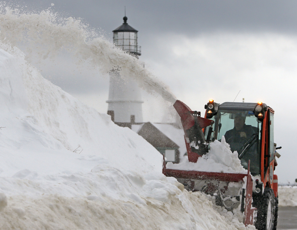 Scott Smart, a public works employee for Cape Elizabeth, clears a sidewalk near Portland Head Light at Fort Williams Park as another winter storm advances on the region.