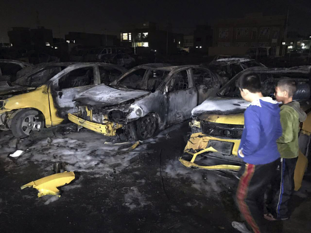 Children gather at the site of a car bomb in a used car dealer's parking lot in the southwestern al-Bayaa neighborhood in Baghdad, Iraq, on Thursday. Dozens of people were killed and wounded.