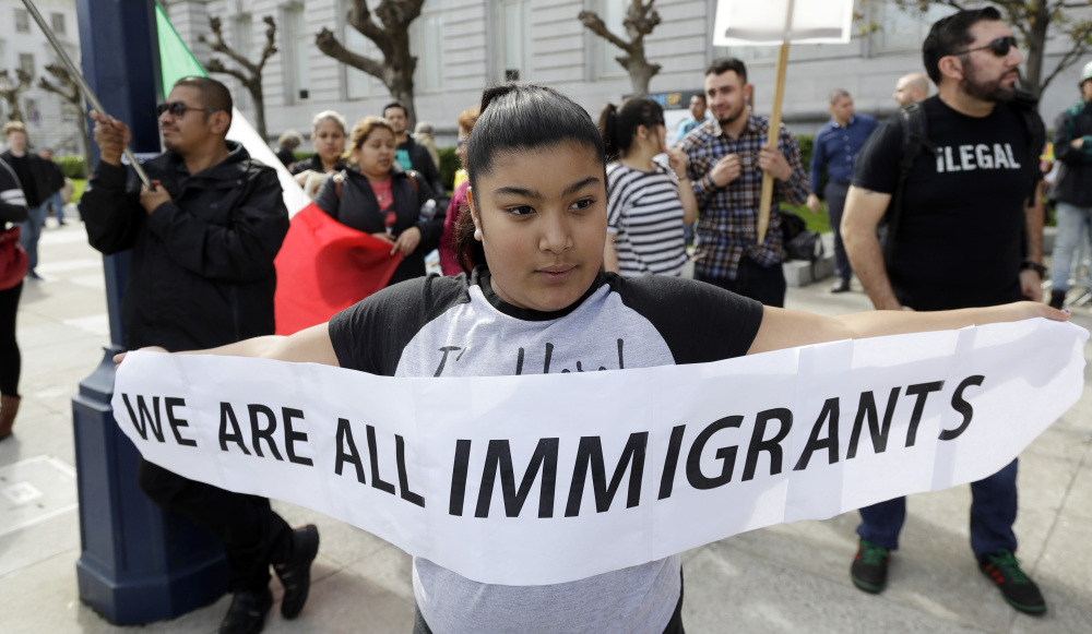 Delilah Gutierrez, 10, left, holds a sign during a protest against President Donald Trump's efforts to crack down on immigration on Thursday in San Francisco.