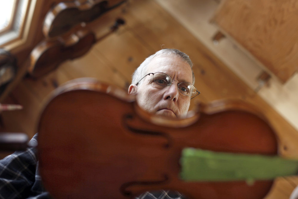Don Roy checks his work after varnishing a work-in-progress fiddle in his Gorham shop.