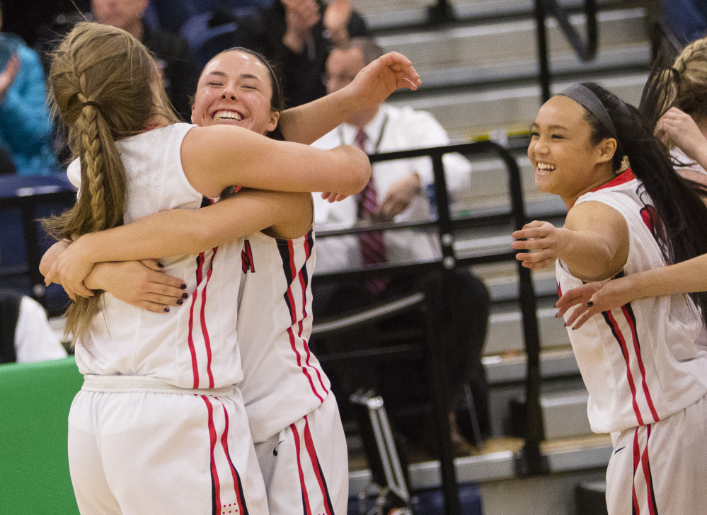 Scarborough players celebrate after their 42-38 win over Thornton Academy in a Class AA South girls' basketball quarterfinal Friday at the Portland Expo.