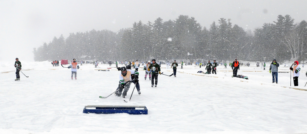One game on one end of the pond, another game on the other end. It's the Maine Pond Hockey Classic in Sidney, and more than 400 players playing with pucks were having a ball.