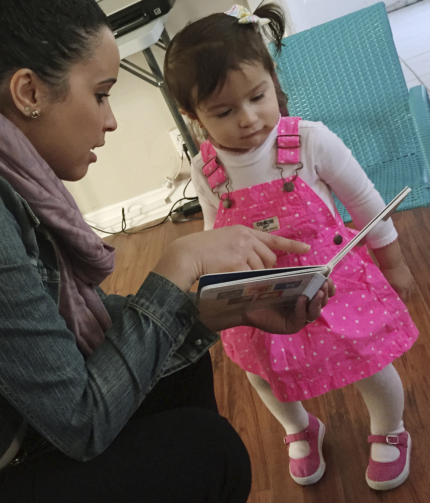 Stephanie Taveras reads a book to Gracey Niebla in Providence, R.I. The city is in the third year of boosting language skills for children from low-income families.