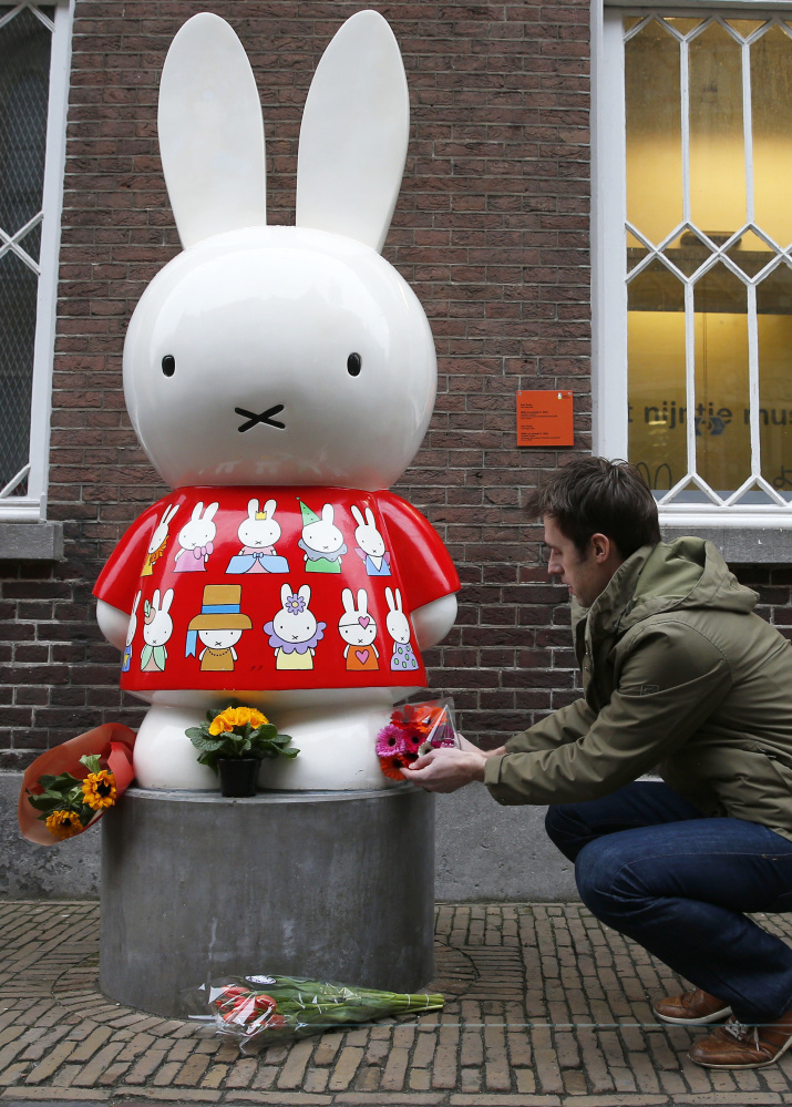 A man places flowers at Miffy's statue outside the Nijntje Museum, or Miffy Museum, in Utrecht, Netherlands, on Friday.
