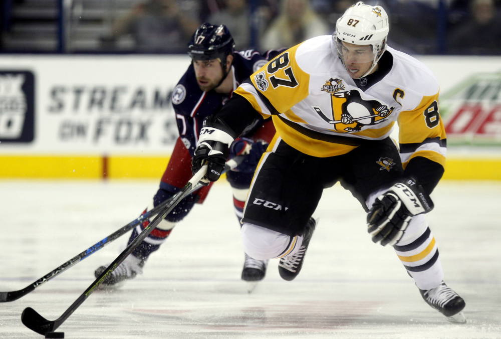 A day after passing 1,000 points with a three-point game, Pittsburgh's Sidney Crosby, right, was held in check Friday night by Brandon Dubinsky, left, and the Blue Jackets. Dubinsky's overtime goal gave Columbus a 2-1 win.
