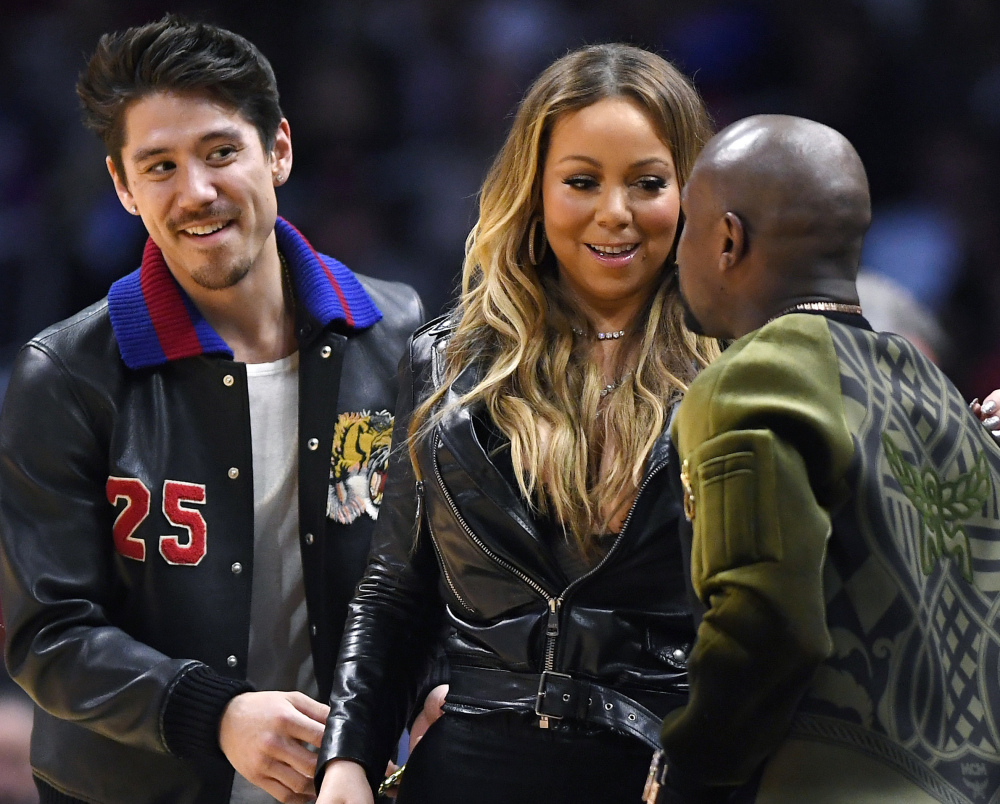 Mariah Carey talks with boxer Floyd Mayweather Jr., right, as her boyfriend, Bryan Tanaka, stands nearby at an NBA game Wednesday in Los Angeles.
