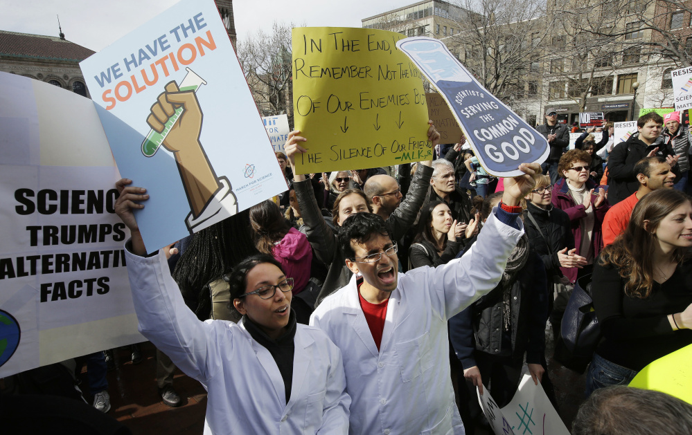 Neuroscientist Shruti Muralidhar, front left, and microbiologist Abhishek Chari, front right, demonstrate Sunday in Boston.