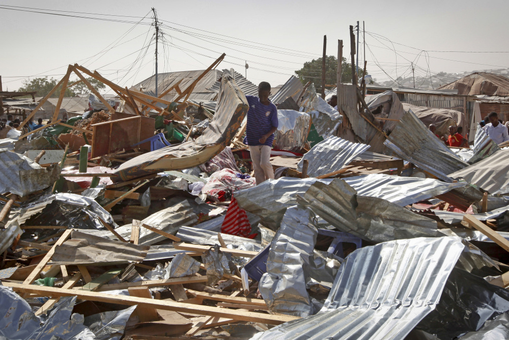A shopkeeper surveys the wreckage after an explosion in Somalia's capital of Mogadishu on Sunday. Police said the blast at a busy market in the western part of the capital tore through shops and food stands, killing 34 people.