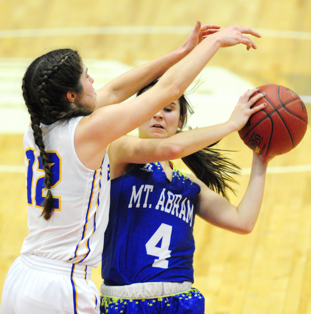 Boothbay's Kate Friant, left, defends Mt. Abram guard Lindsay Huff during a Class C South quarterfinal Monday at Augusta Civic Center. Boothbay advanced with a 60-21 victory.