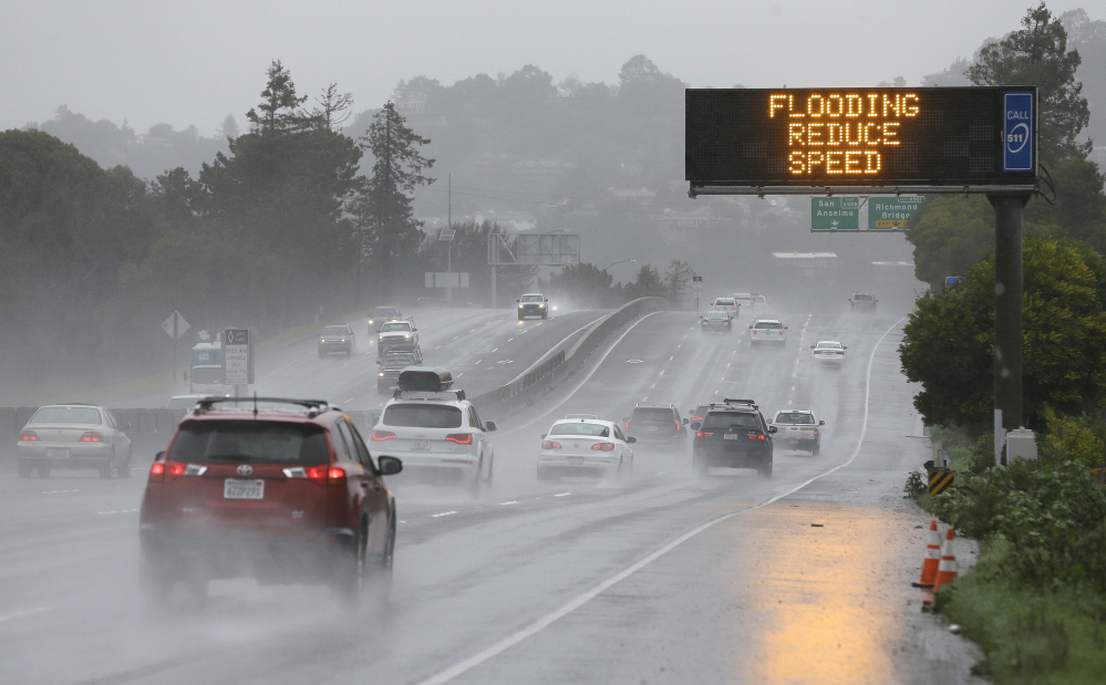 A sign warns motorists of flooding Monday on northbound Highway 101 in Corte Madera, Calif. Heavy downpours are swelling creeks and rivers and bringing threats of flooding in the state's already soggy northern and central regions.