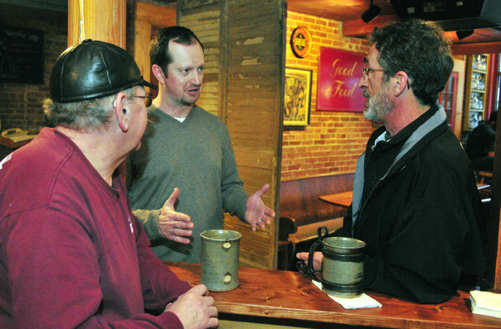 Kurt Leonard, left, and Leo Fecteau chat with front-of-house manager Casey Hynes Wednesday at the Liberal Cup in Hallowell. Hynes says the wage hike has left the pub with less money to pay nonservers.