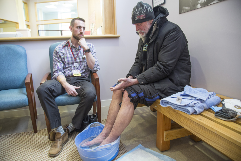 Dr. Adam Normandin listens to Brian French at the 20 Portland St. clinic as the homeless man bathes his feet in warm water and Epsom salt to treat symptoms of frostbite.