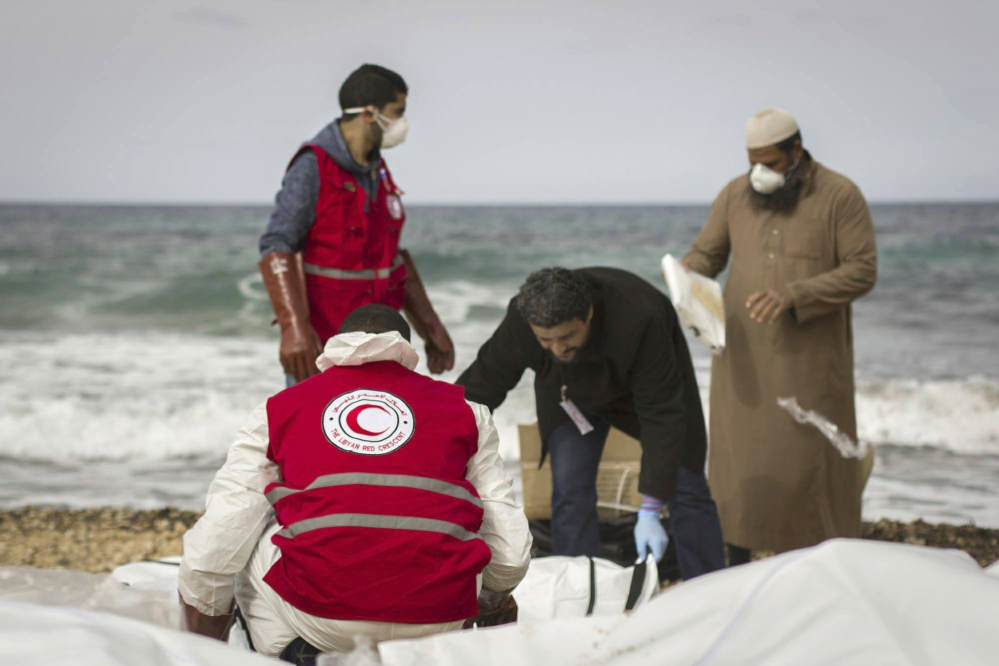 This photo provided by The International Federation of Red Cross and Red Crescent Societies, shows Libyan Red Crescent workers recovering bodies of people that washed ashore, near Zawiya, Libya.