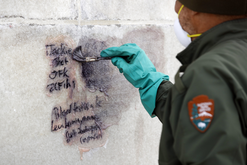 A U.S. Park Service employee works to clean graffiti off the Washington Monument on Tuesday in Washington.