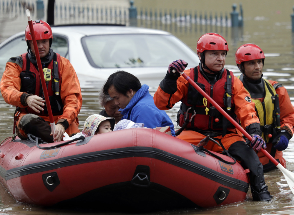 Rescue crews ferry residents from a flooded neighborhood Tuesday in San Jose, Calif. About half the state remains under flood, wind and snow advisories.
