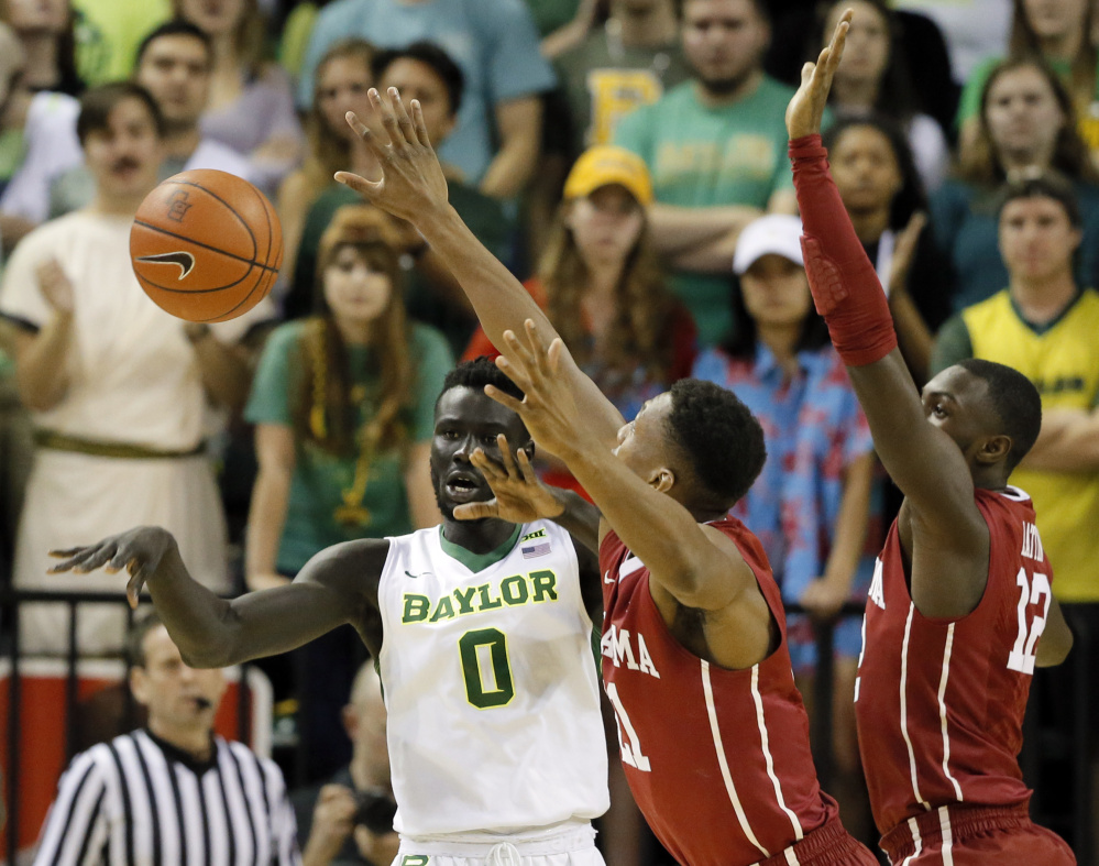 Baylor forward Jo Lual-Acuil Jr. passes the ball under pressure from Oklahoma's Dante Buford, center, and Khadeem Lattin during Baylor's 60-54 home win Tuesday.