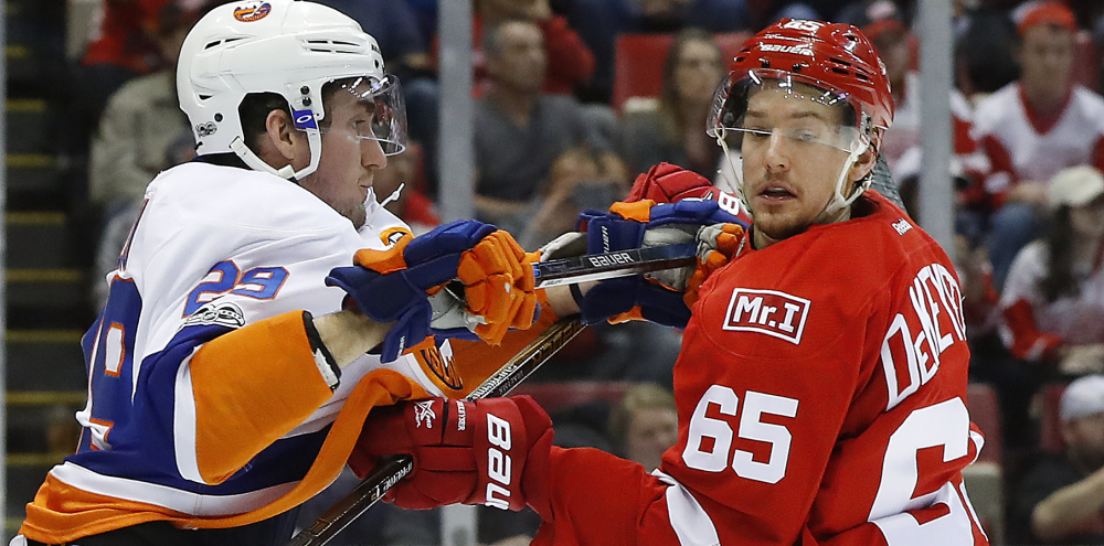Brock Nelson of the Islanders and Detroit's Danny DeKeyser get their sticks up as they battle Tuesday night in Detroit.