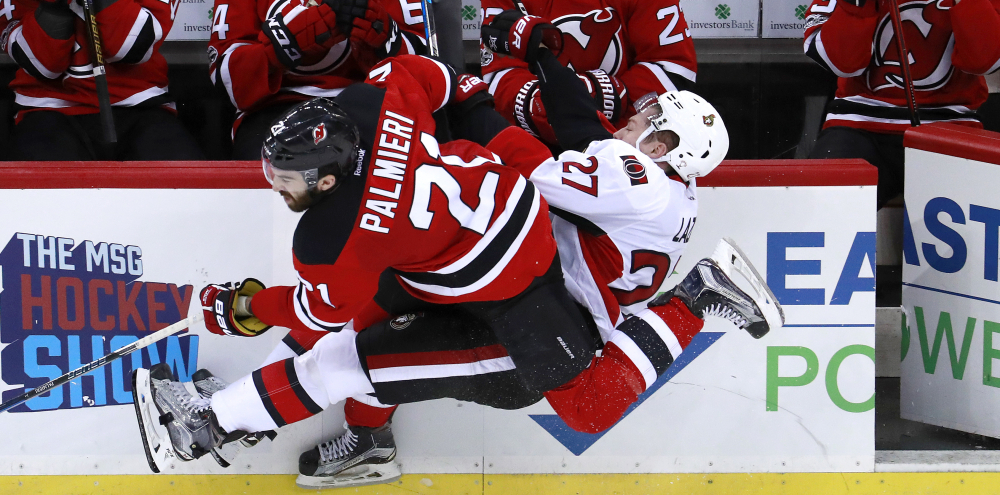 Kyle Palmieri of the Devils checks Ottawa's Curtis Lazar near the bench in the third period of Tuesday night's game at Newark, N.J. Ottawa, which was playing without three of its top six forwards, beat the Devils, 2-1.