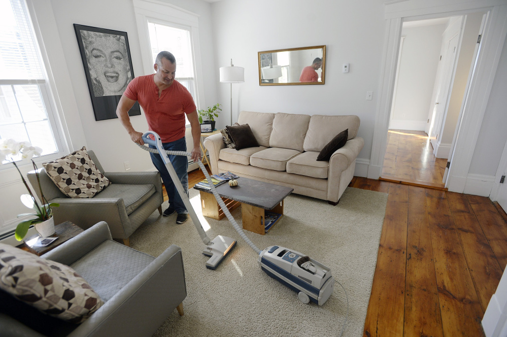 PORTLAND, ME - OCTOBER 8: Gary Wagner vaccums the half of his home he rents out on Airbnb after guests had left Thursday, October 8, 2015. (Photo by Shawn Patrick Ouellette/Staff Photographer)