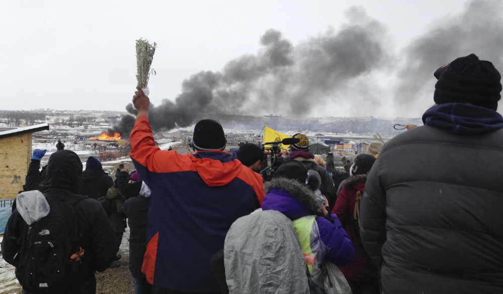 A fire burns in the background as opponents of the Dakota Access pipeline leave their protest camp near Cannon Ball, N.D. on Wednesday. Authorities were preparing to shut down the camp before spring flooding season.