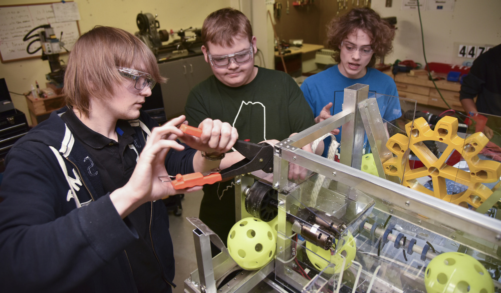 From left, Bryce Bragdon of Windsor, Michael Crochere of Chelsea and William Fahy of Hallowell put finishing touches on their robot Tuesday at the Ballard Center in Augusta.