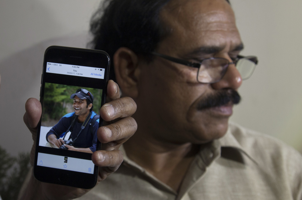 A man shows a picture of Alok Madasani, an engineer who was injured in the shooting Wednesday night in a crowded suburban Kansas City bar, on a mobile phone as Madasani's father, Jaganmohan Reddy, talks to the media at his residence in Hyderabad, India, on Friday.