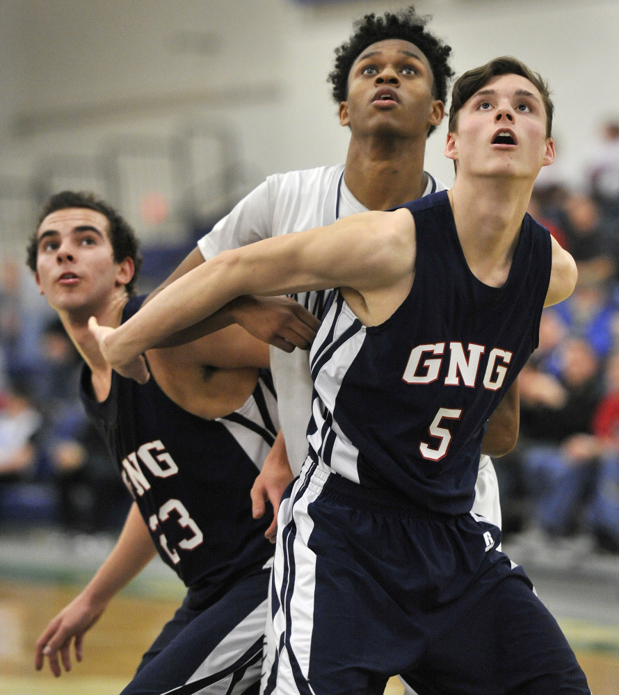 "Yarmouth's NaJee McQueen, center, battles with John Villanueva, left, and Tanner Mann of Gray-New Gloucester during Yarmouth's win Feb. 18. A reader praises this photo for showing ""their emotions as well as the court action."""