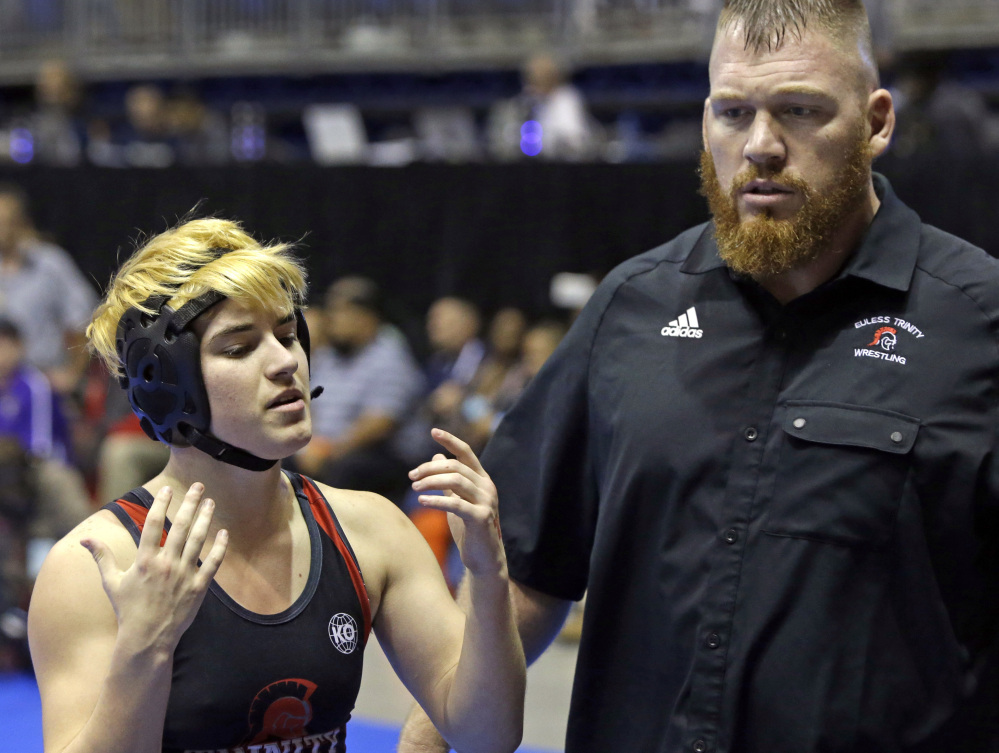 Mack Beggs talks with his coach Travis Clark. Beggs was born female and is transitioning to male. Some say the testosterone treatments Beggs has been taking make him too strong to wrestle fairly with girls.