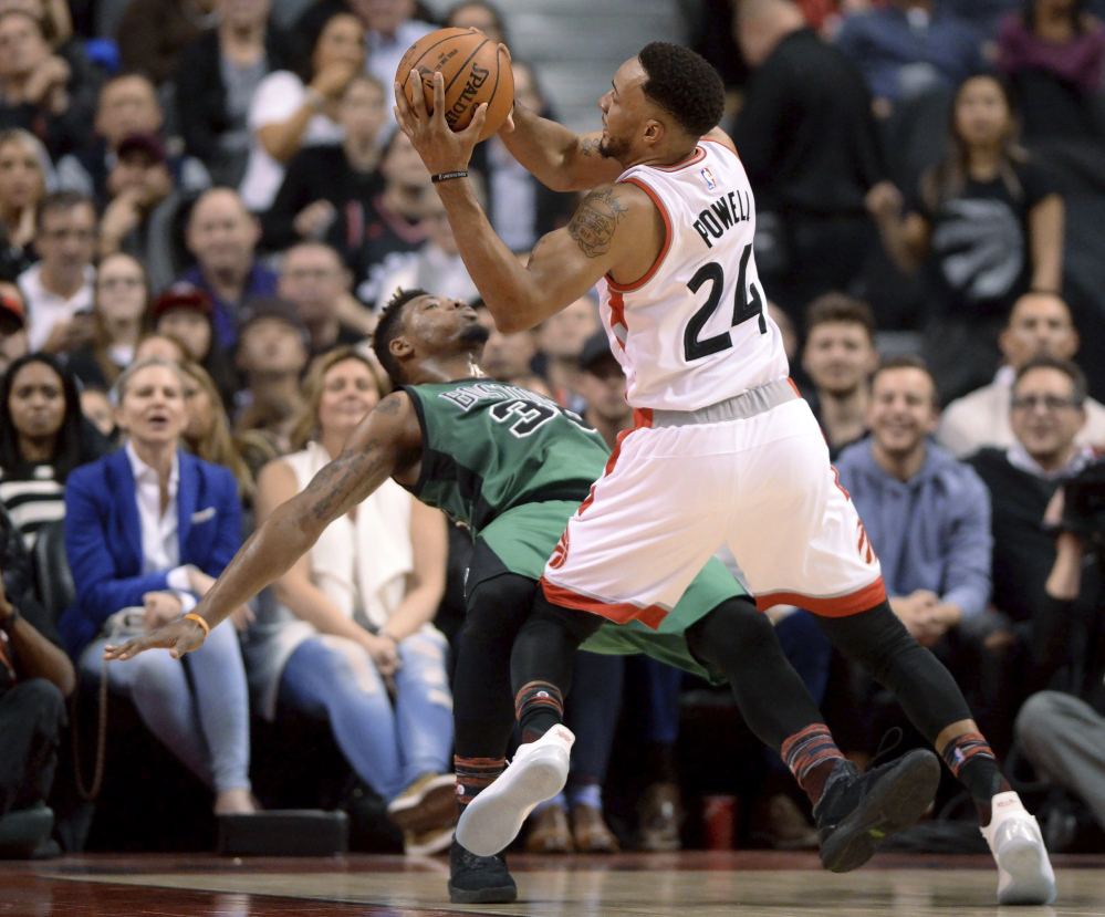 Toronto's Norman Powell collides with Boston's Marcus Smart and is called for charging in the first half of Friday night's game at Toronto.