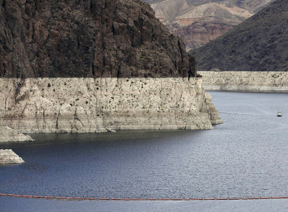 "A ""bathtub ring"" marks the high water mark as a recreational boat approaches Hoover Dam along Black Canyon on Lake Mead, the largest Colorado River reservoir, in 2013."