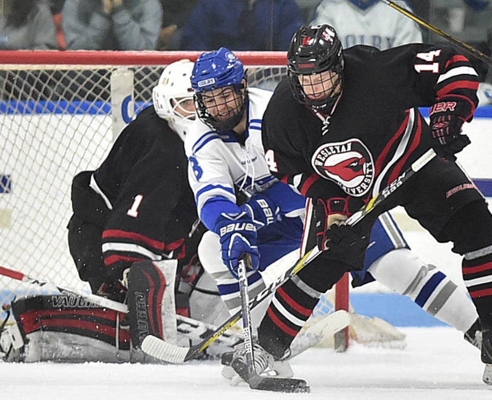 Colby's Devin Albert, center, battles for the puck with Wesleyan's Spencer Fox, right, in front of Cardinals goalie Dawson Sprigings on Saturday during their NESCAC quarterfinal at Waterville. Wesleyan won 5-4.