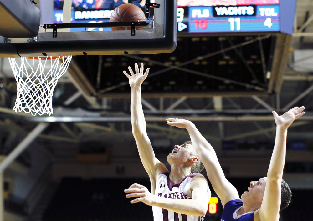 Greely's Ryan Twitchell sneaks past Emmett Hamilton of Falmouth during the Class A South boys' basketball final Saturday night at Cross Insurance Arena. Twitchell led top-ranked Greely to a 47-26 victory.