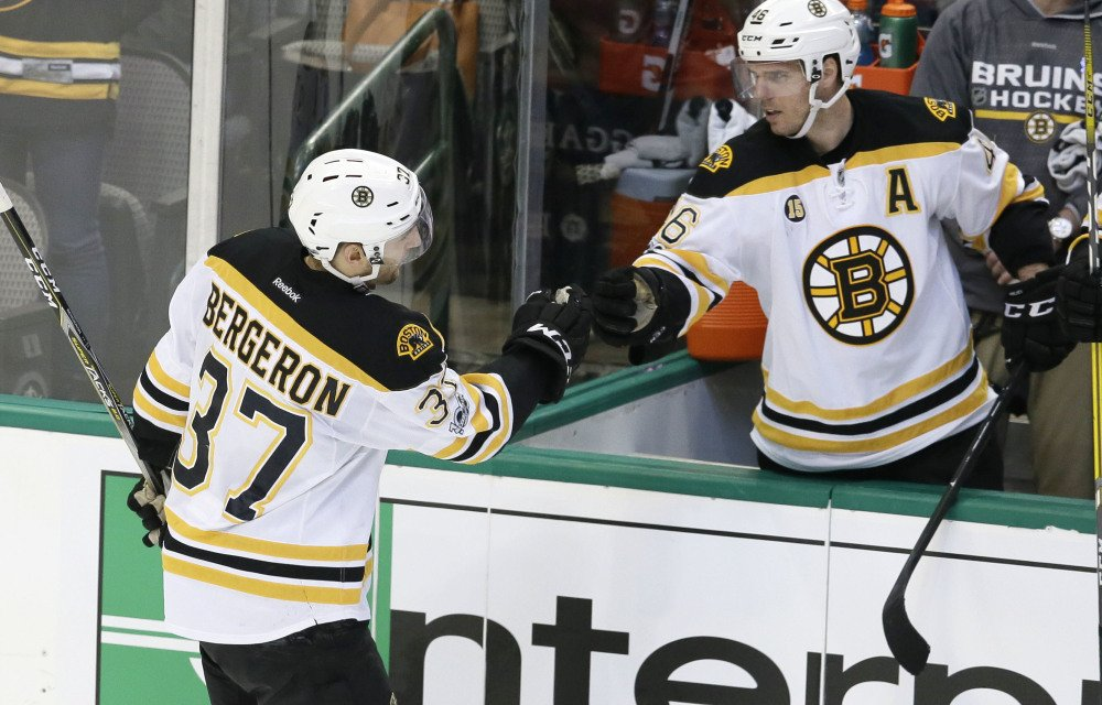 Boston Bruins center Patrice Bergeron (37) is congratulated by teammate David Krejci (46) after scoring during the second period against the Dallas Stars on Sunday in Dallas. The Bruins won 6-3. (Associated Press/LM Otero)