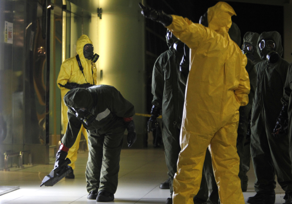 "A hazardous materials crew scans the decontamination zone Sunday at Kuala Lumpur International Airport 2 in Sepang, Malaysia, where Kim Jong Un's half brother was attacked with a lethal poison. After the two-hour sweep, a police official said the terminal is ""free from any form of contamination"" and declared it a ""safe zone."""
