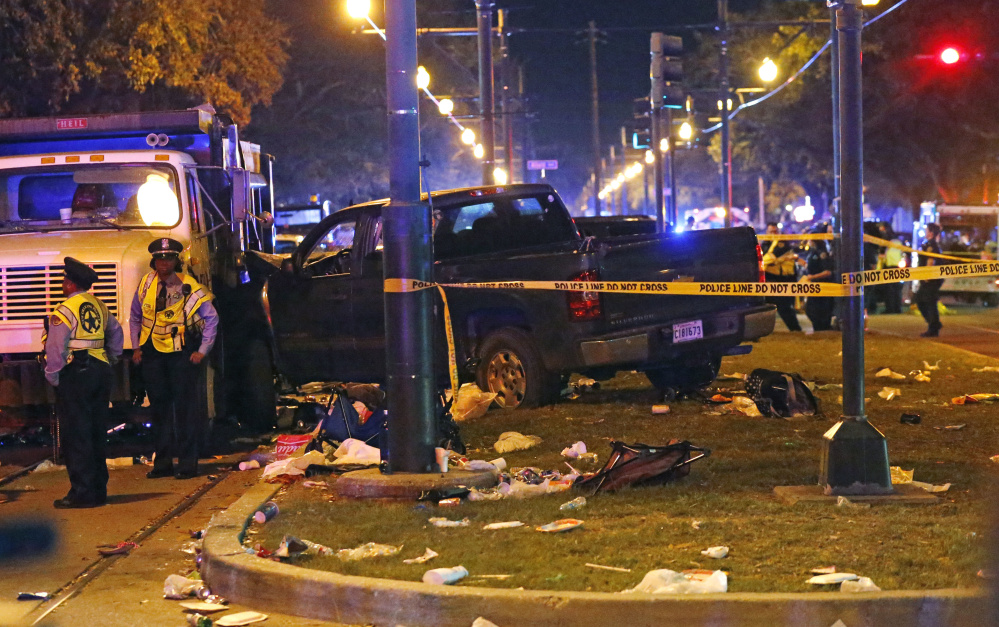 Police stand next to a pickup truck that slammed into a crowd, causing multiple injuries, before coming to a stop against a dump truck during a Mardi Gras parade in New Orleans.