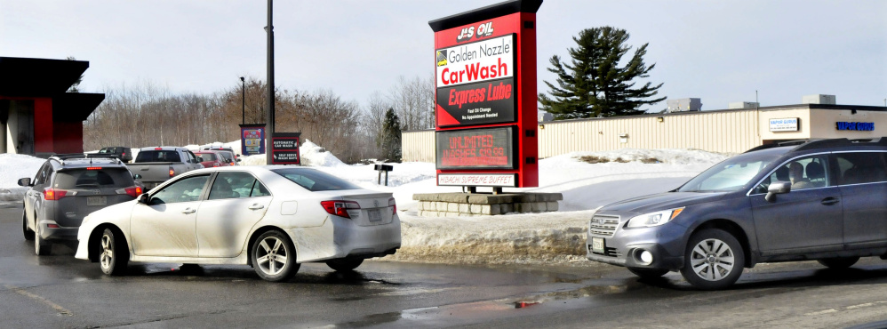 Vehicles idle in a line on Kennedy Memorial Drive in Waterville to enter the J&S Oil car wash on Wednesday, a day after police warned motorists not to park along the road while waiting in line for the car wash.