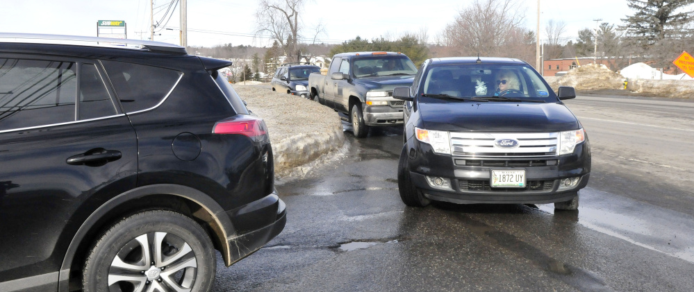 Vehicles on Kennedy Memorial Drive in Waterville wait to enter the J&S Oil car wash on Wednesday.