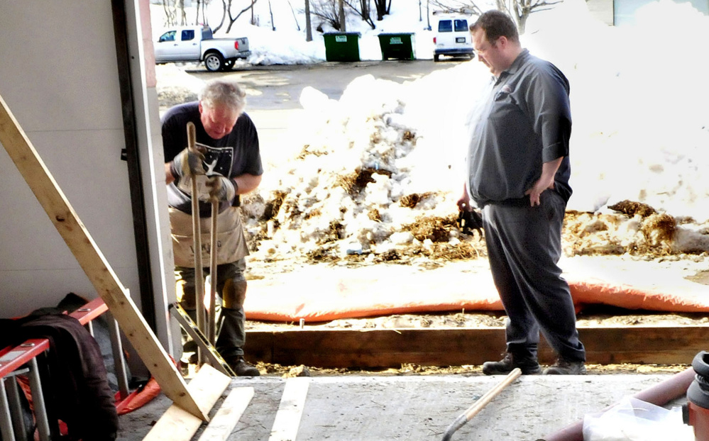 Chet Ficker, right, owner of Kennebec Express Lube, works with his father, Chris Ficker, to rebuild the floor. Their business, which will open again in March, is the only other car wash in Waterville.
