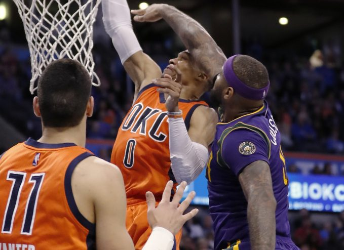 Oklahoma City guard Russell Westbrook is fouled by New Orleans forward DeMarcus Cousins, right, during the Thunder's 118-110 win Sunday in Oklahoma City.