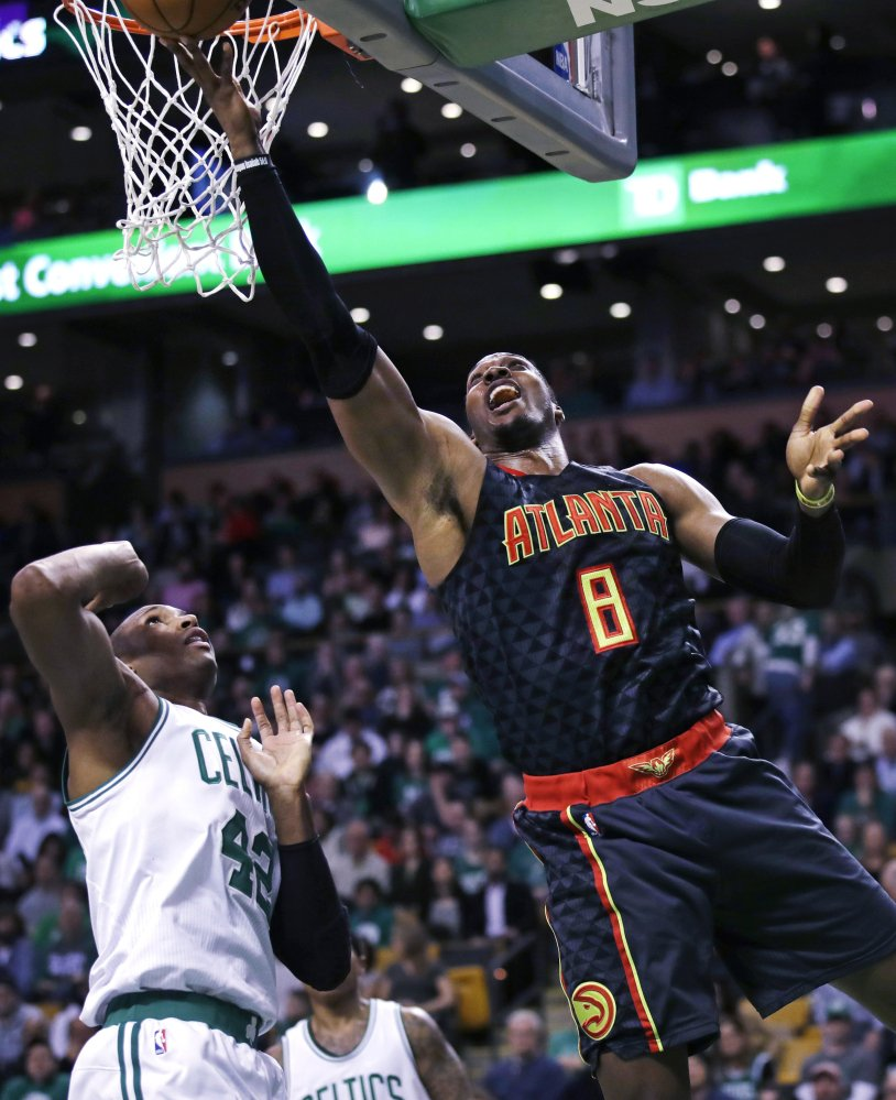 Atlanta center Dwight Howard drives past Celtics center Al Horford in the second quarter. Howard was ejected in the second half, but his ejection didn't keep Atlanta from routing the Celtics.