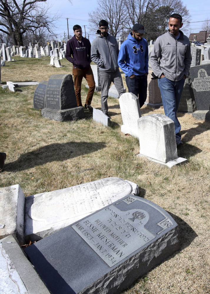 Volunteers from the Ahmadiyya Muslim Community survey damaged headstones at Mount Carmel Cemetery in Philadelphia on Monday. More than 100 headstones have been vandalized at the Jewish cemetery.