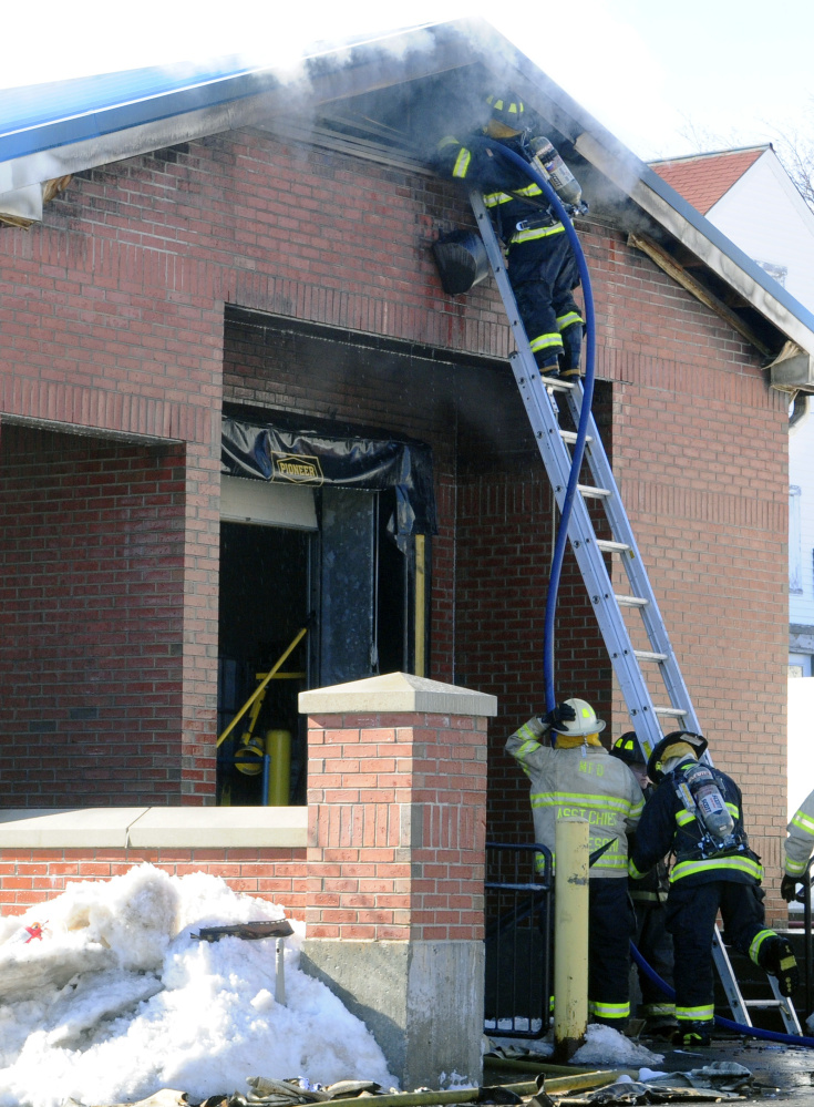 Firefighters work last week at the Winthrop post office, which will be torn down after a fire gutted the building. Plans call for rebuilding the facility at the same location.