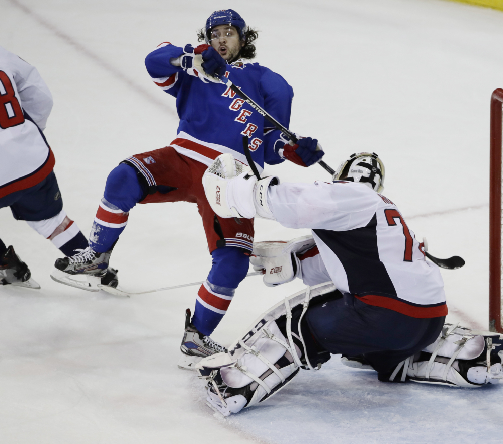 Mats Zuccarello of the Rangers trips over Washington Capitals goalie Braden Holtby in the third period Tuesday night in New York. The Capitals won 4-1.