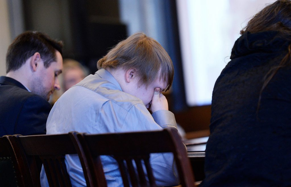 Dylan Collins covers his face as friends and family members of the victims speak at Collins' sentencing hearing Monday in York County Superior Court.